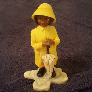 Girl in yellow rain coat and hat with umbrella